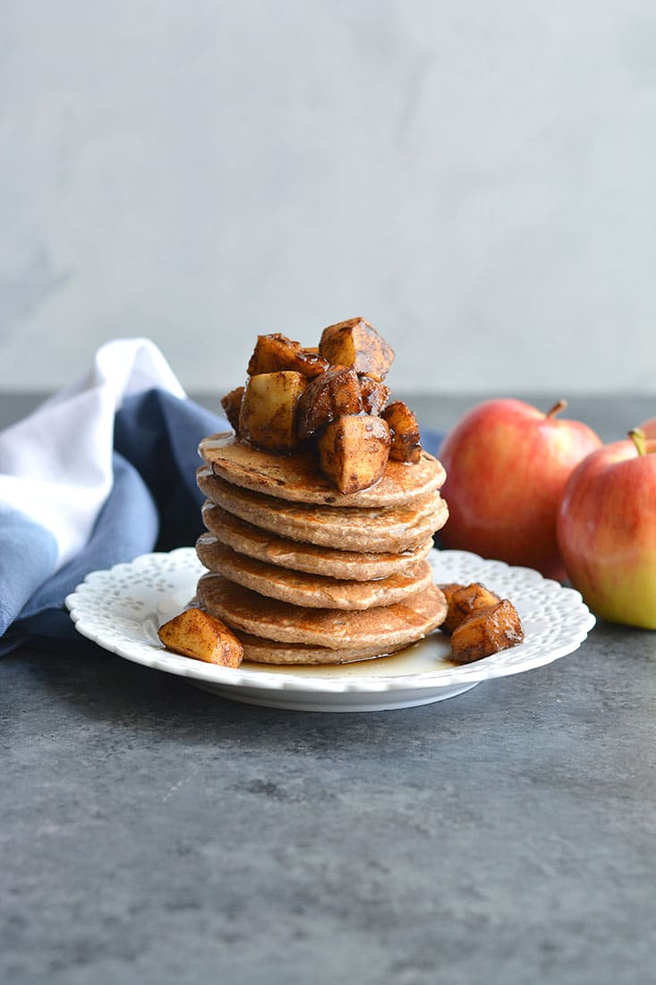Apple Cinnamon Greek Yogurt Pancakes! Light, fluffy whole grain pancakes topped with caramelized apples. These lightened up pancakes are gluten free and make an irresistible fall breakfast! Gluten Free + Low Calorie