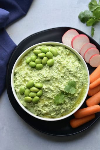 Edamame Hummus made with 4 ingredients. A simple, high protein snack made in a blender with Greek yogurt and fresh herbs. A healthy, gluten free protein packed snack for any day of the week! Gluten Free + Low Calorie