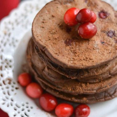 Creamy Cranberry Cocoa Pancakes that taste like hot cocoa! High in antioxidants & packed with protein, this crepe-like stack is bursting with sweetness. A guaranteed crowd pleaser! Gluten Free + Low Calorie