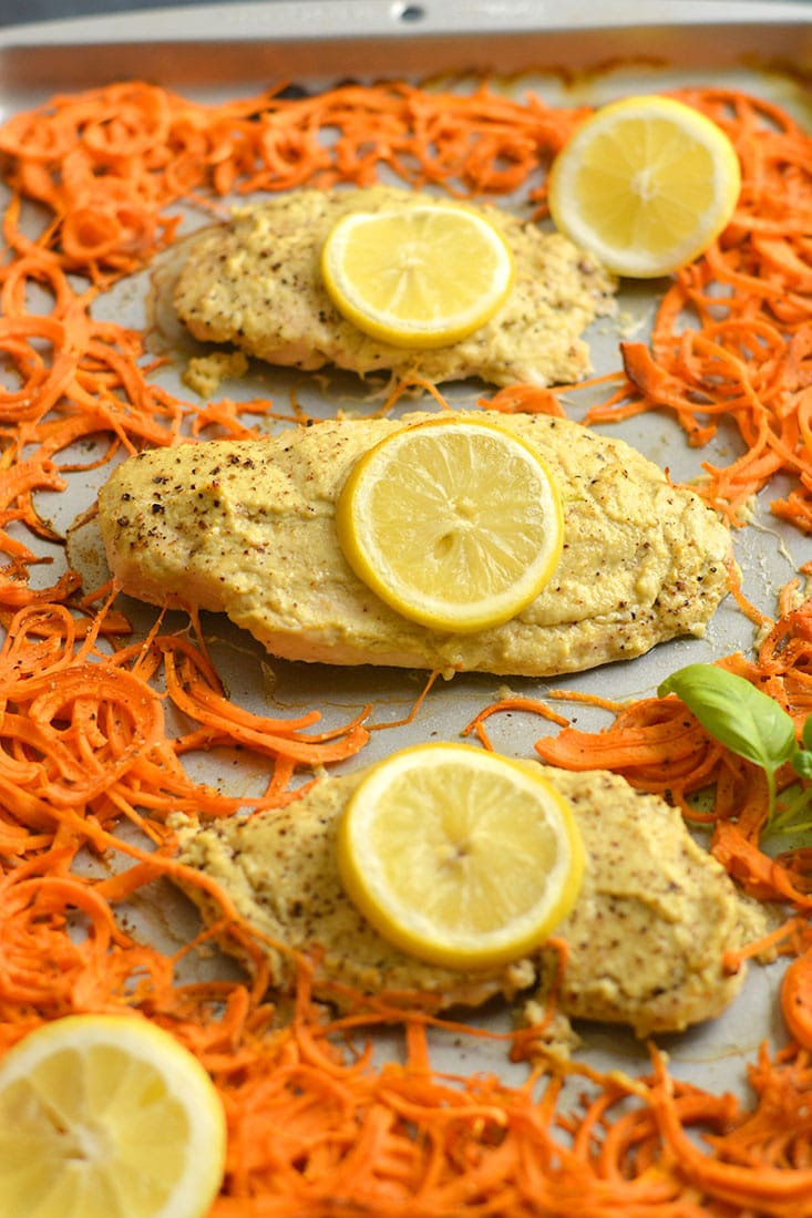 Sheet Pan Hummus Chicken marinated in Paleo zucchini hummus turns boring chicken into a flavorful meal. Paired with spiralized sweet potato for a french fry like side. All made on one sheet pan in 20 minutes! Paleo + Gluten Free + Low Calorie