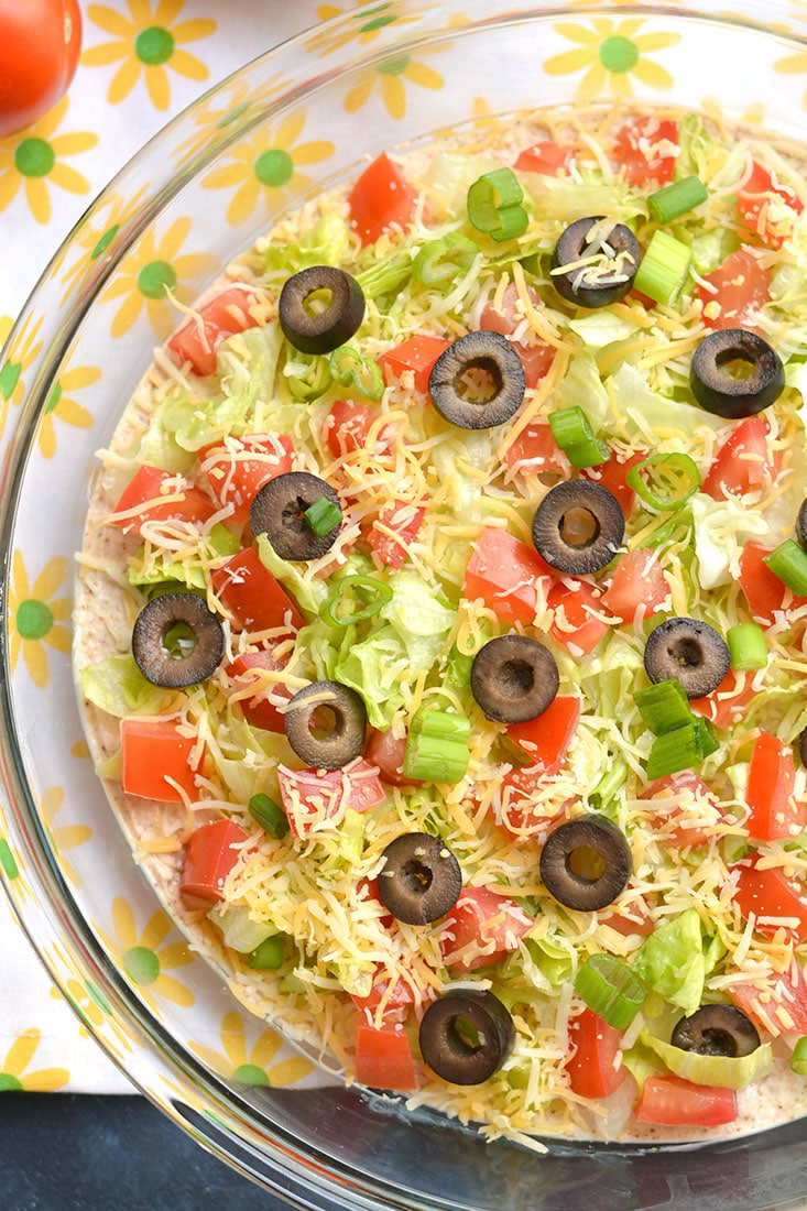 Healthy Taco Dip made with tangy, protein packed Greek Yogurt & homemade taco seasoning! Your guests will have no idea this flavorful party dip is healthy! Gluten Free + Low Calorie