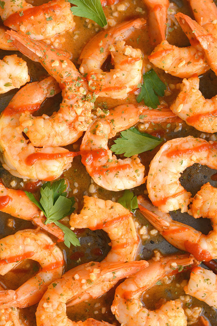 Spicy Sriracha Shrimp made two ways! Tender shrimp tossed in garlic, lime and Sriracha then cooked to perfection. A low carb,Gluten Free and Paleo meal made in less than 15 minutes!Gluten Free + Low Calorie + Paleo