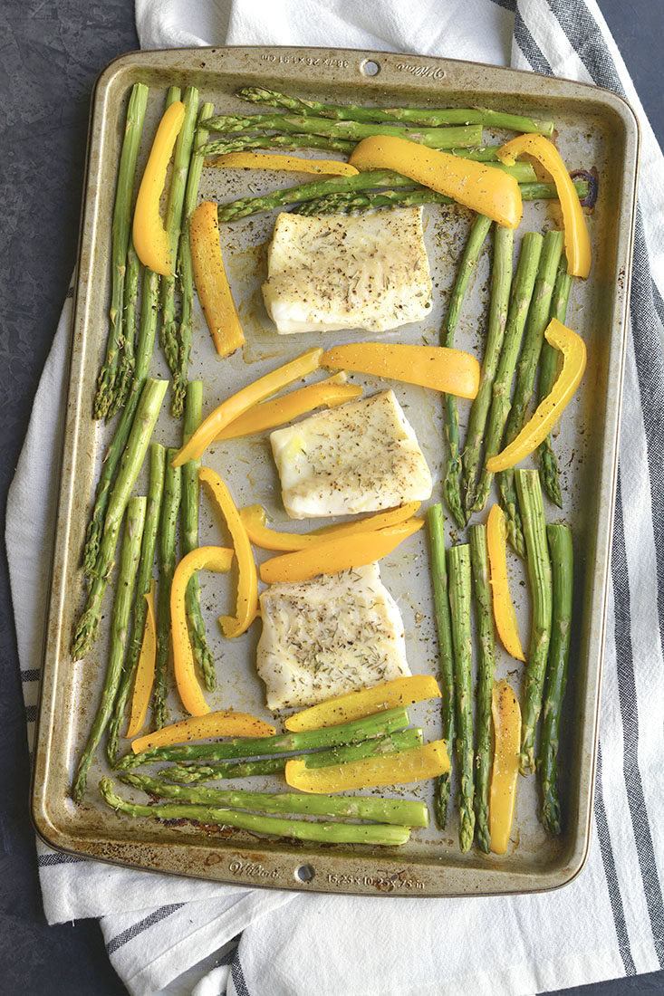 Sheet Pan Cod with Veggies! Baked cod with garlic & herbs with roasted veggies. A light, easy, Paleo meal that takes less than 30 minutes to make & prep. Baked cod never was so easy or so good! Gluten Free + Low Calorie + Paleo + Whole30
