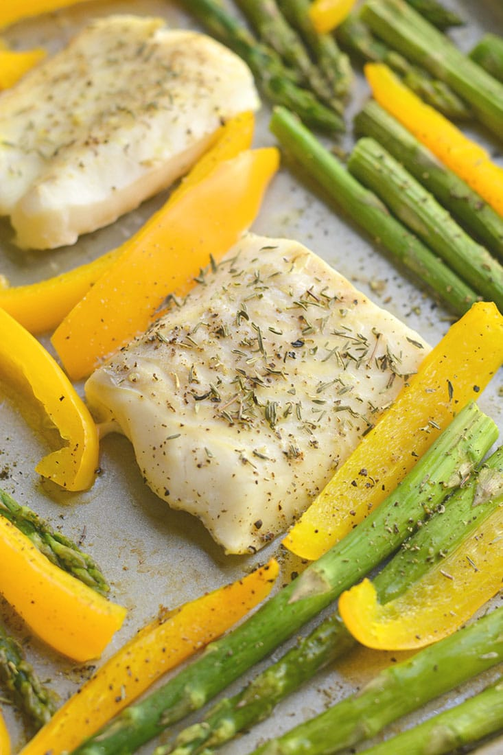 Sheet Pan Cod with Veggies! Baked cod withgarlic & herbs with roasted veggies. A light, easy, Paleo meal that takes less than 30 minutes to make & prep. Baked cod never was so easy or so good! Gluten Free + Low Calorie +Paleo + Whole30
