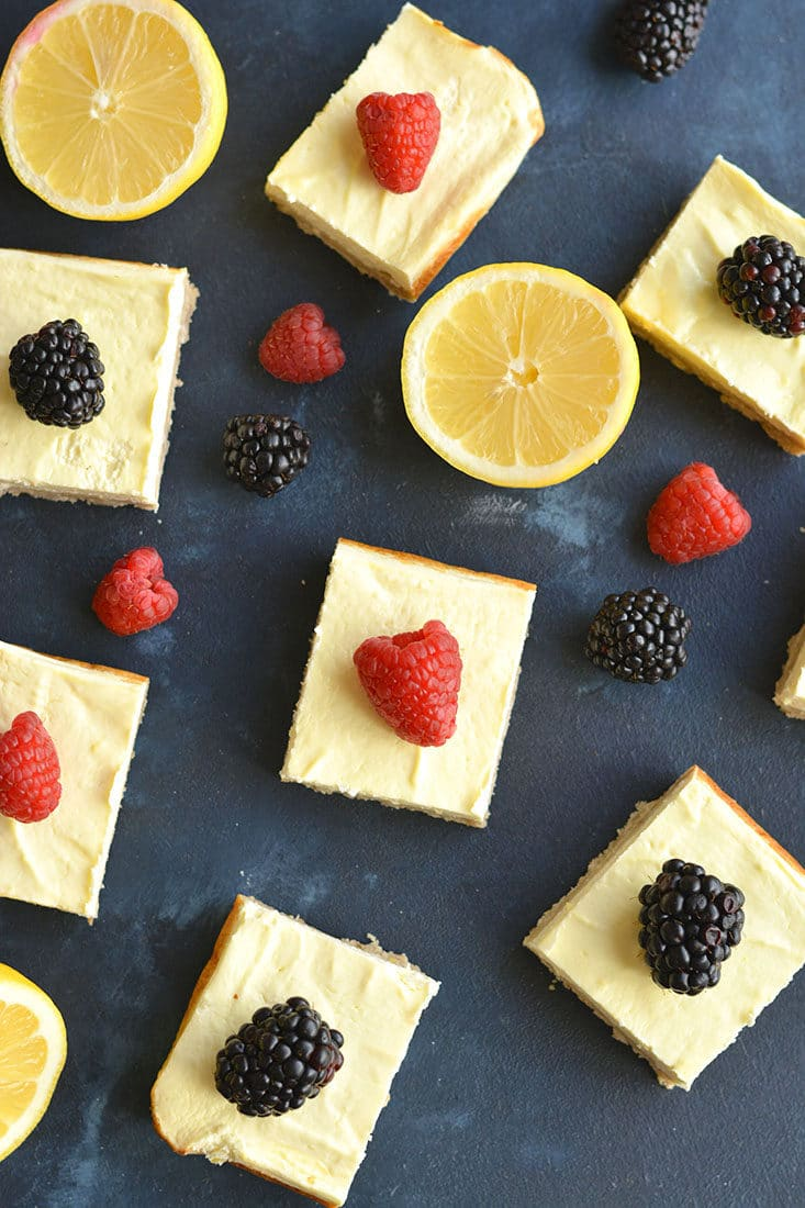 Skinny Greek Yogurt Lemon Bars! These creamy bars have a gluten free shortbread crust with a stevia sweetened Greek yogurt custard layer on top that's bursting with lemon flavor! These lightened up bars are baked to perfection for the ultimate low calorie dessert! Gluten Free + Low Calorie