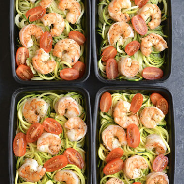 Meal Prep Shrimp Zucchini Noodles! Zesty lemon garlic shrimp is topped over zucchini noodles with sliced tomatoes. Baked on a sheet pan in under 10 minutes! A light, fresh and satisfying low carb meal to take with you on the go! Paleo + Gluten Free + Low Calorie