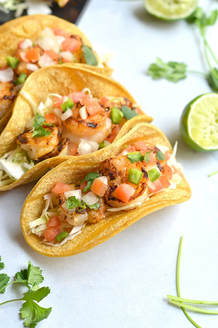 10 Minute Grilled Shrimp Tacos! This lightened up recipe shows you how to do tacos healthier and in a breeze. Grilling shrimp produces delicious flavor and can be easily done with a grill pan. A healthy dinner for busy weeknights or weekend BBQ's! Gluten Free + Low Calorie with a Paleo option