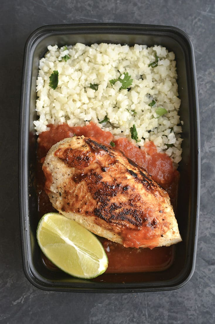 Meal Prep Margarita Chicken! This lightened up chicken is marinated and cooked in a skillet with spices. Paired with cilantro lime cauliflower rice and salsa for an EASY, low carb dinner or lunch. Perfect for busy week days! Low Carb + Paleo + Low Calorie + Gluten Free