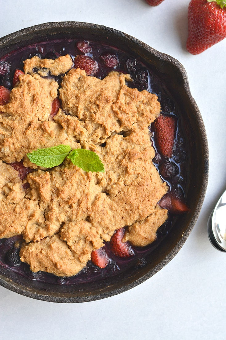 Low Sugar Berry Cobbler is the ultimate summertime treat! Made in one skillet with glycemic friendly ingredients. Low in calories and higher in protein than traditional cobblers, this warm weather dessert is sure to be your new favorite treat. Paleo + Gluten Free Options