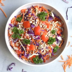 Thai Asian Salad with nut free sunflower dressing! A loaded detox salad with cabbage, carrots, and bell peppers tossed in a spicy Asian dressing. Healthy fat and carbs unite! Serve as a side salad or add your favorite lean protein for a complete meal. Vegan + Paleo + Low Calorie + Gluten Free