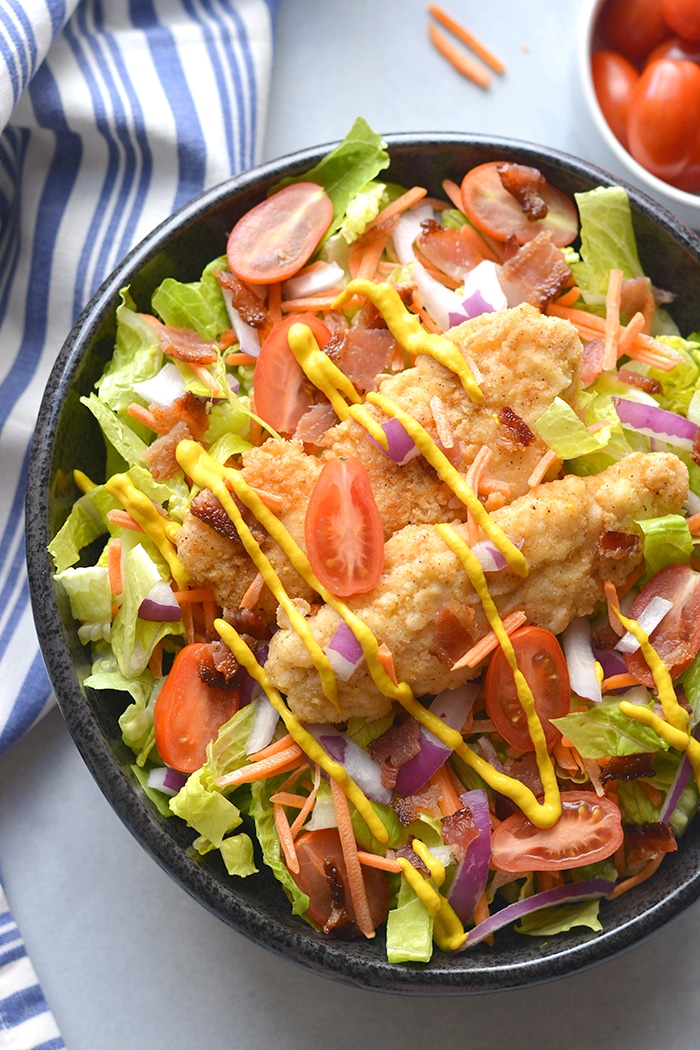 Paleo Honey Mustard Chicken Salad! Crispy almond flour tenders served over a bacon salad with a lightened up honey mustard dressing. A healthier mustard chicken that's family approved! Gluten Free + Paleo + Low Calorie