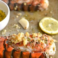 Herby Lemon Garlic Lobster never tasted this good! Baked in the oven with a lighter herby lemon garlic sauce, this simple recipe is one you'll want to make again and again. Perfect easy meal for date night! Whole30 + Paleo + Gluten Free + Low Calorie + Low Carb