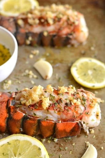 Herby Lemon Garlic Lobster never tasted this good!Baked in the oven with a lighter herby lemon garlic sauce, this simple recipe is one you'll want to make again and again. Perfect easy meal for date night! Whole30 + Paleo + Gluten Free + Low Calorie + Low Carb