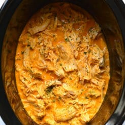 Healthy Crockpot Buffalo Chicken with just 4 ingredients! Chicken slow cooked in a secret high protein sauce make super tender and juicy shredded chicken. An easy recipe for meal prep. Low Carb + Low Calorie + Gluten Free