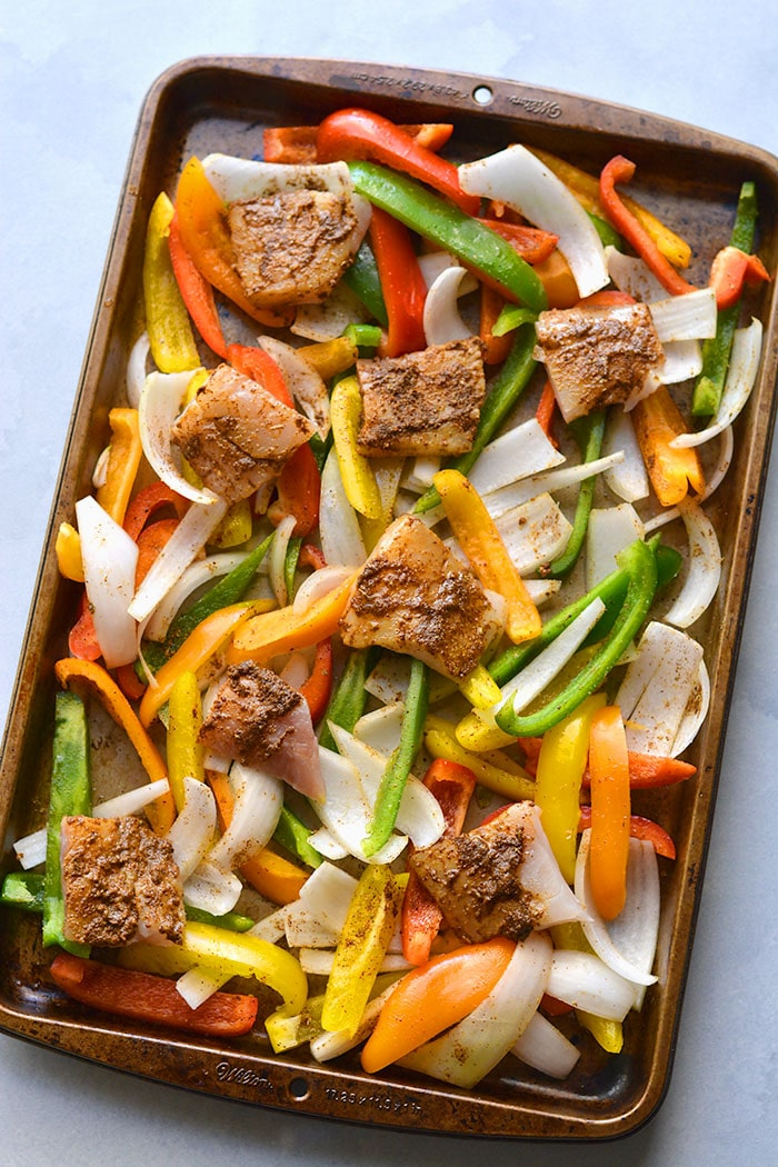 Healthy Sheet Pan Fish Fajitas! This dinner recipe is made in under 30 minutes with veggies and seasoned fish! An easy, healthy weeknight meal that's perfect for feeding a crowd or one. Paleo + GlutenFree + Low Calorie + Low Carb