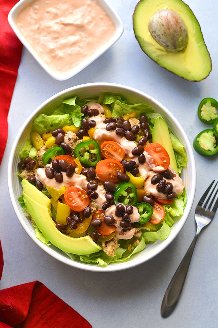 This Healthy Taco Salad is a low calorie meal packed with veggies, ground turkey, black beans and topped with a Greek yogurt salsa dressing. A super simple meal that's filling, high in protein and fiber to keep cravings away.