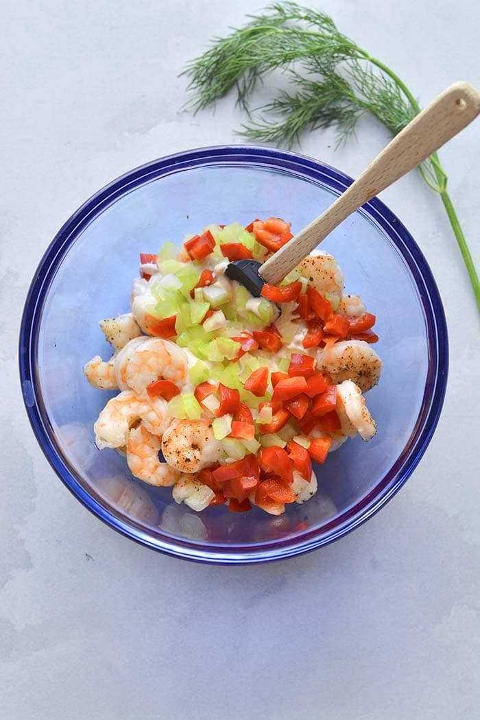 mixing bowl with ingredients for making a shrimp salad with Greek yogurt