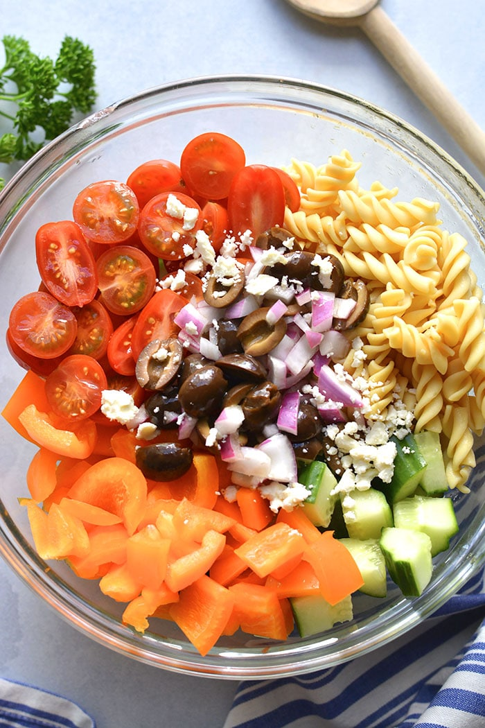 pasta salad ingredients in a glass mixing bowl